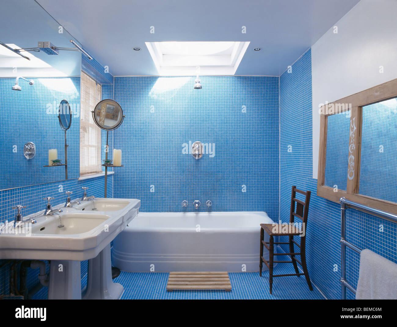 Double white basins in modern blue mosaic tiled bathroom with bath ...