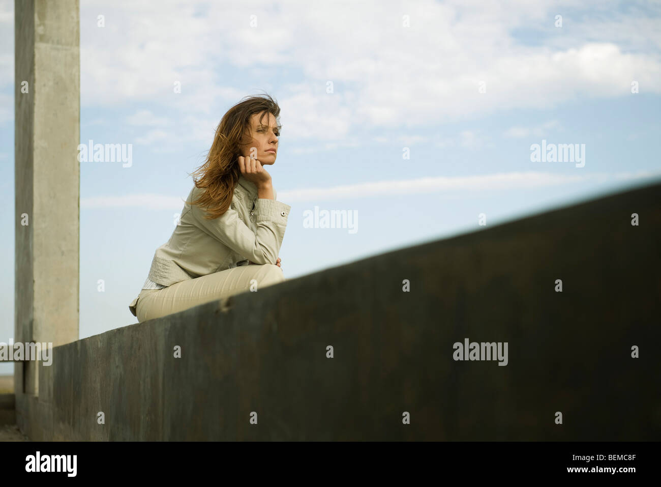 Woman leaning on elbow contemplatively looking away - Stock Image