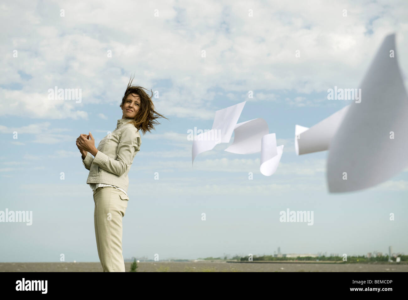 Woman outdoors watching documents caught in wind fly away - Stock Image