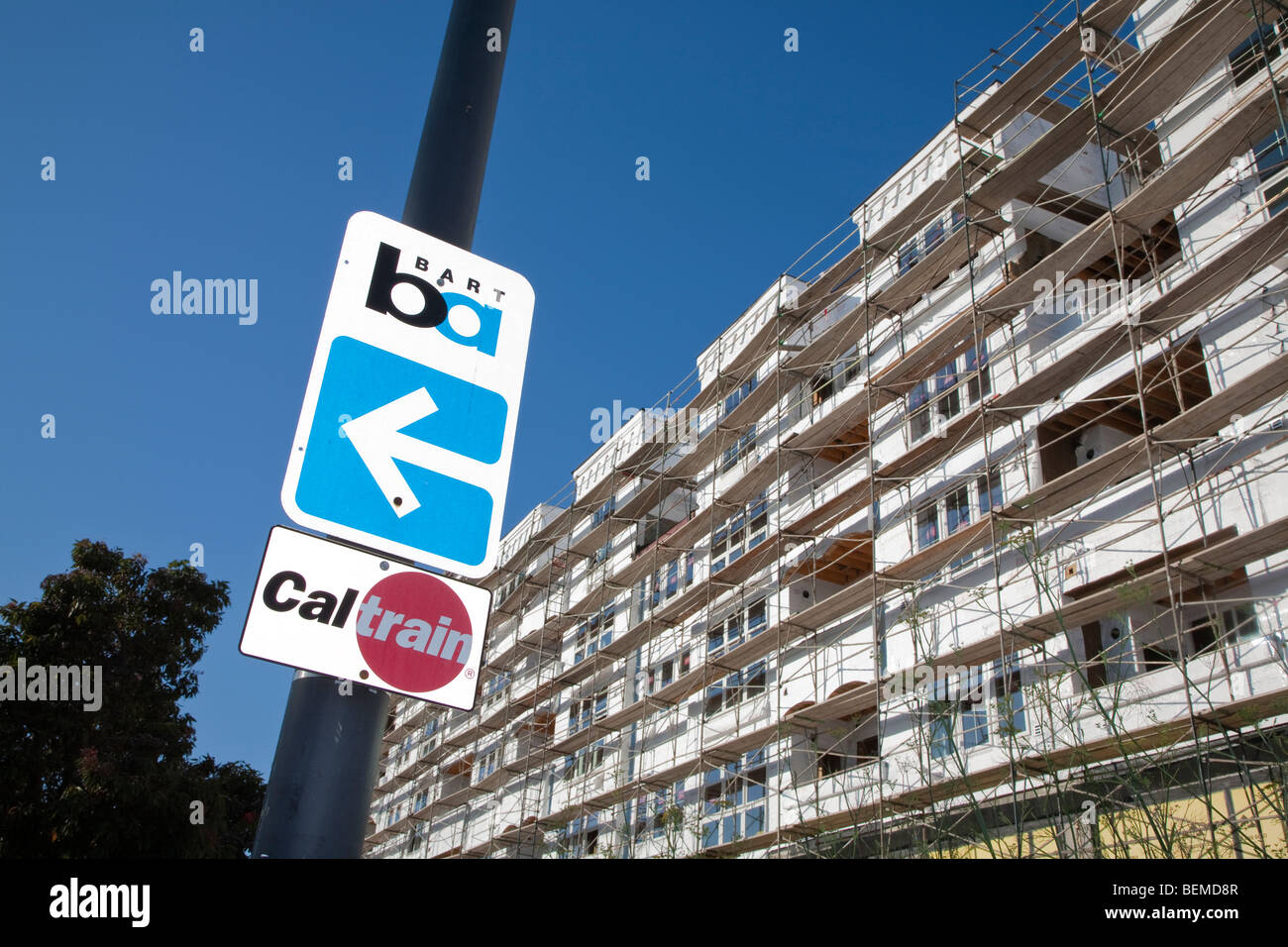 A low angle view of BART and Caltrain road signs by a scaffolded condo. Millbrae, California, USA Stock Photo