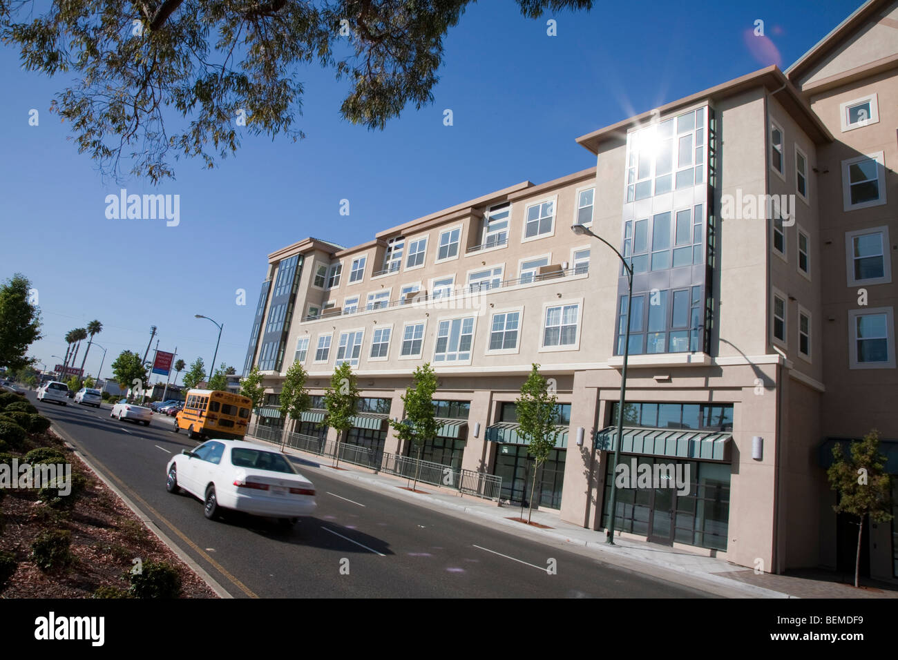 A tilted view of a building with condos and office space, viewed from a divided road. Park Broadway, El Camino Real, Stock Photo