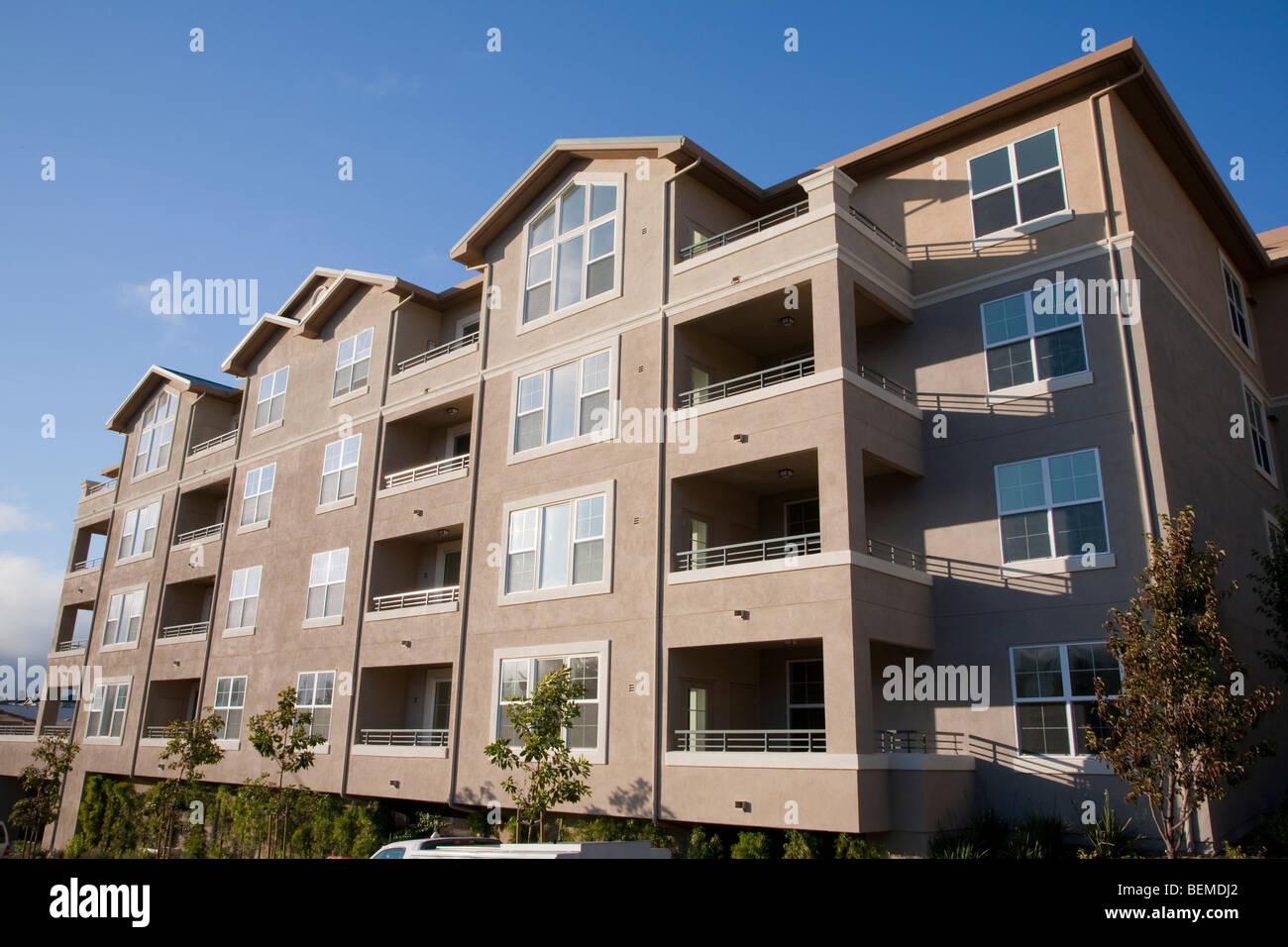 A newly built compact housing development lined with trees. Park Broadway on El Camino Real in Millbrae, CA, USA Stock Photo