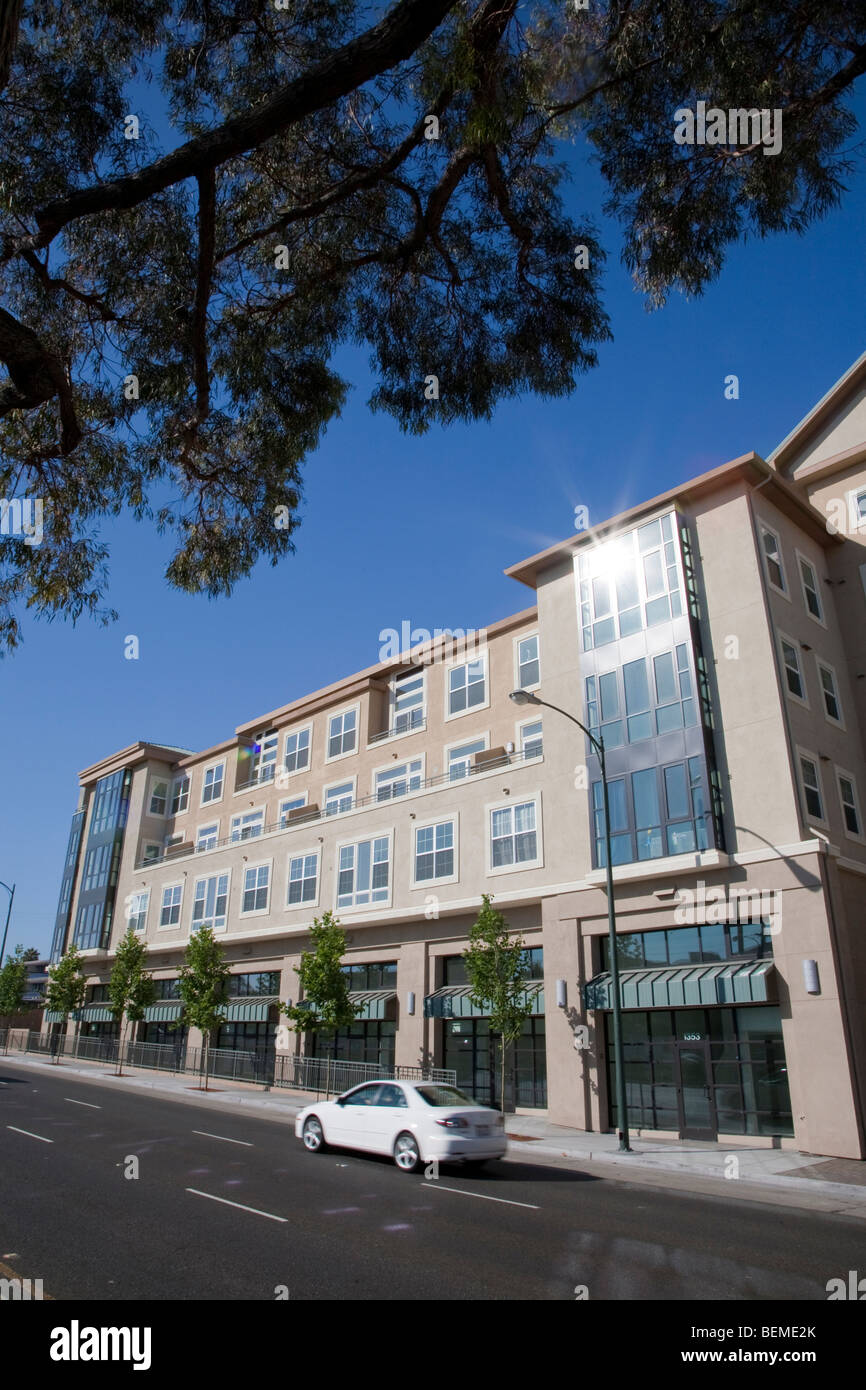 A tilted view of a building with condos and office space, viewed from a divided road. Park Broadway on El Camino Stock Photo