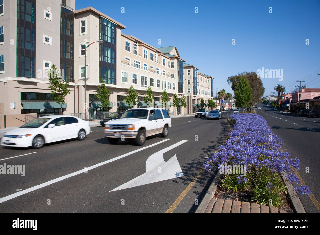 Cars on El Camino Real pass a mixed use housing development. Landscaped divided roadway. Millbrae, CA, USA Stock Photo