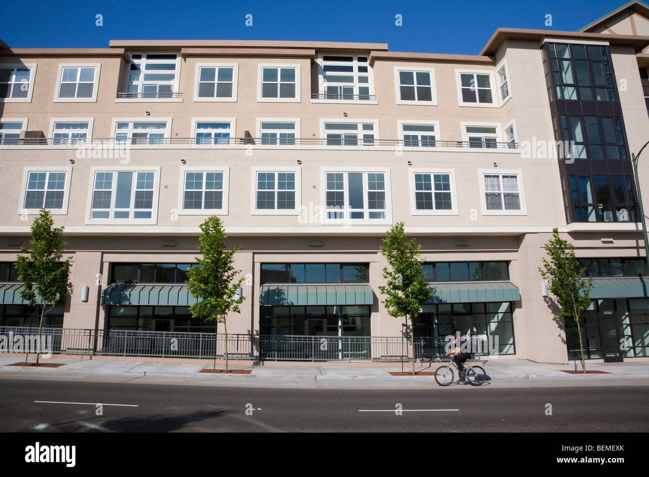 Bicyclist rides in front of mixed use housing development. Residential condominiums and office, retail space. CA Stock Photo
