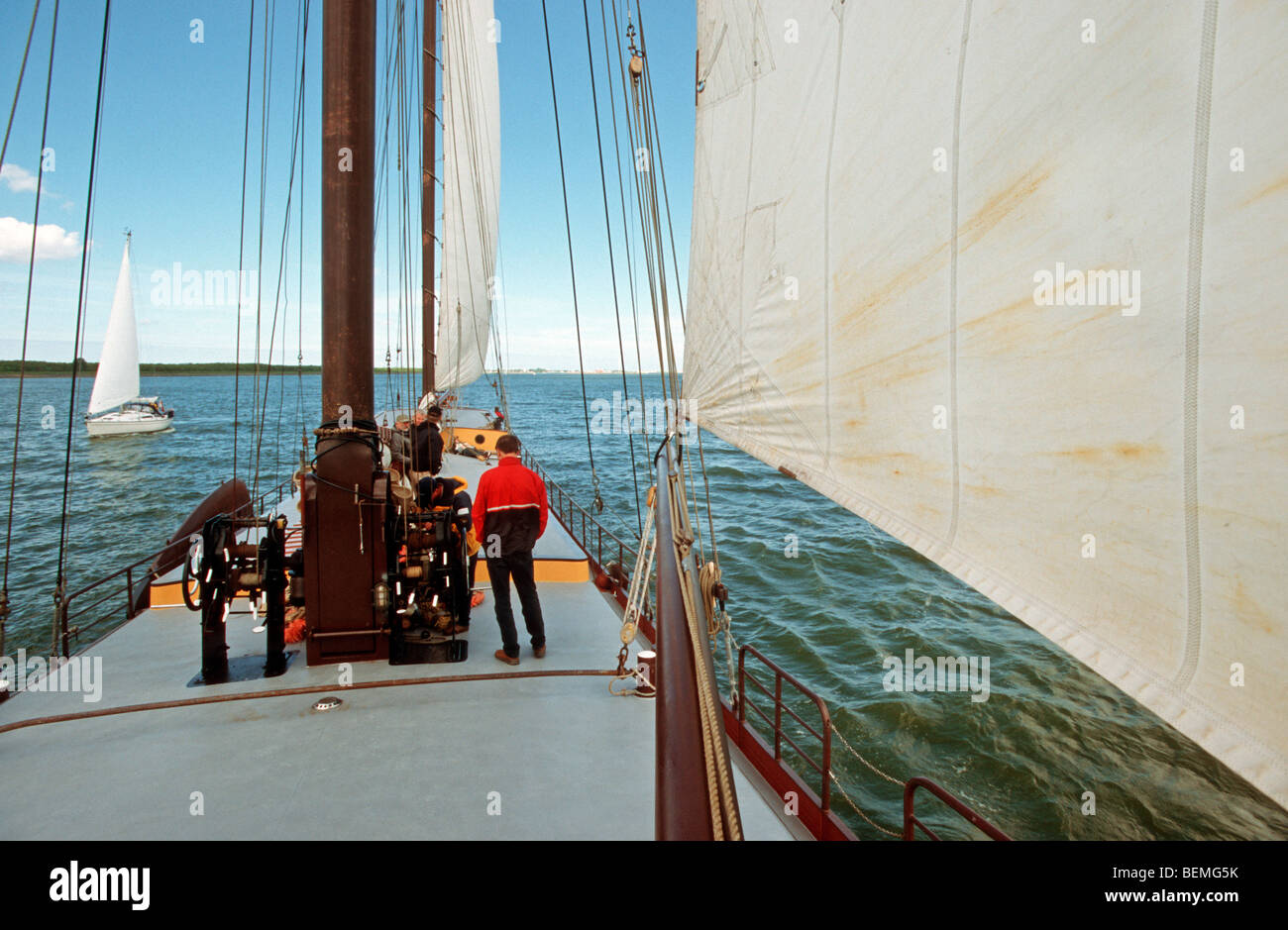 Yachtsman on clipper sailing on the Wadden Sea along the Frisian islands, the Netherlands - Stock Image