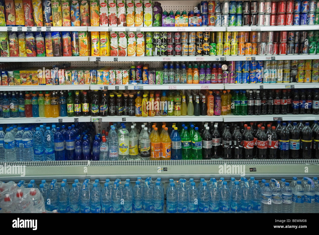 Shelves with lots of different soft drinks, like colas, fruit sodas, juices and water in a Supermarket in Cyprus - Stock Image