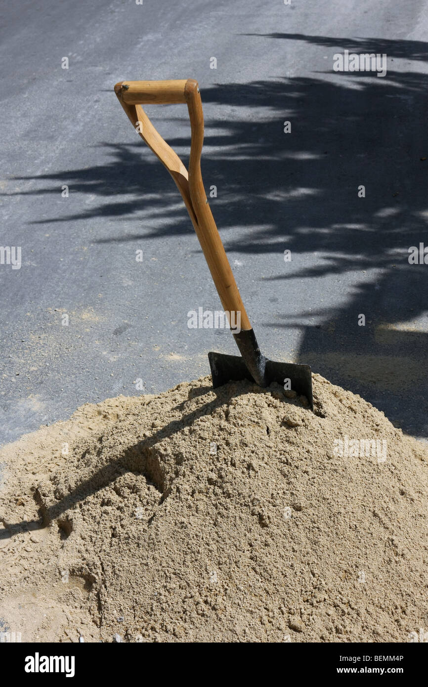 Spade in a pile of sand on a street. - Stock Image