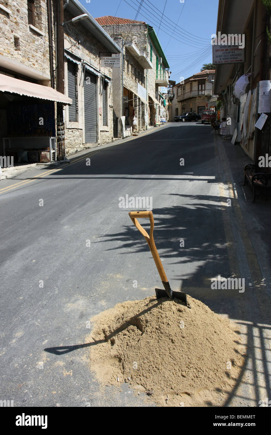 Spade in a pile of sand on a street in the small village of Lefkara, Cyprus. - Stock Image