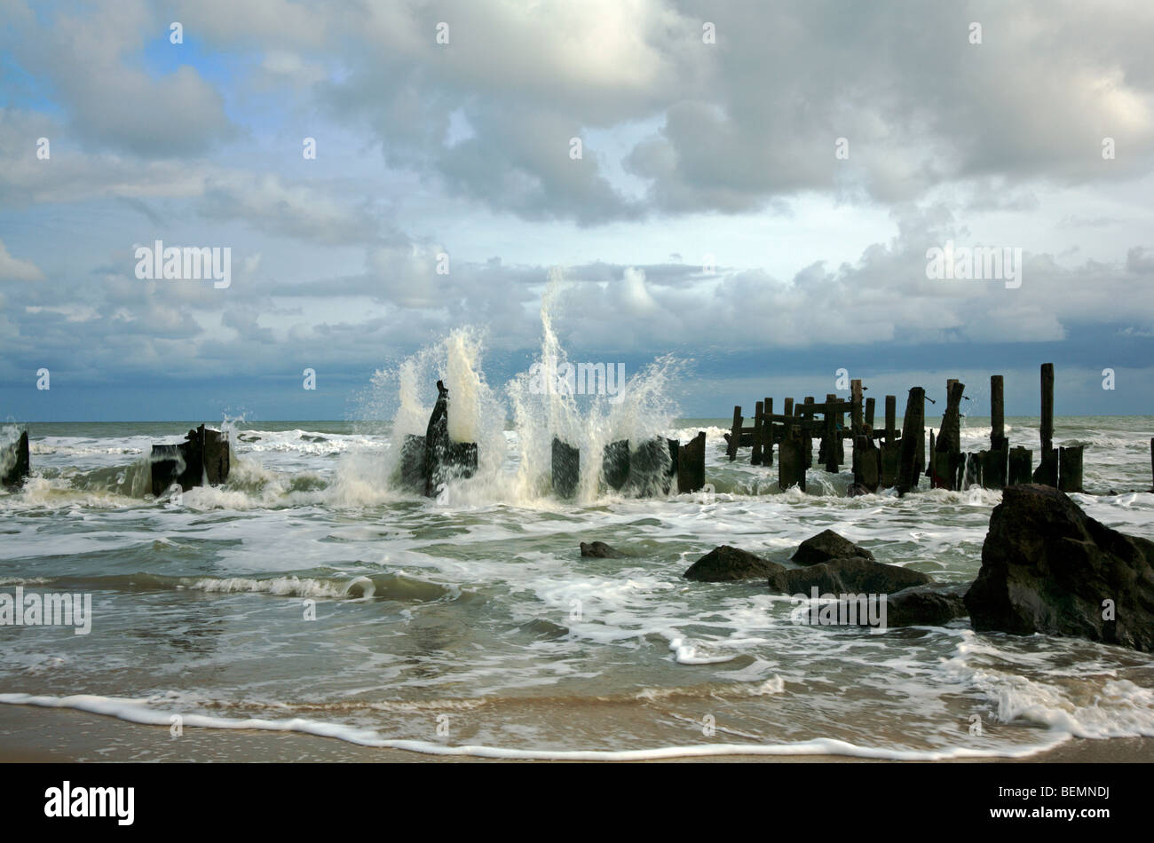 Old breakwaters at Happisburgh, Norfolk, United Kingdom, being pounded by waves. - Stock Image