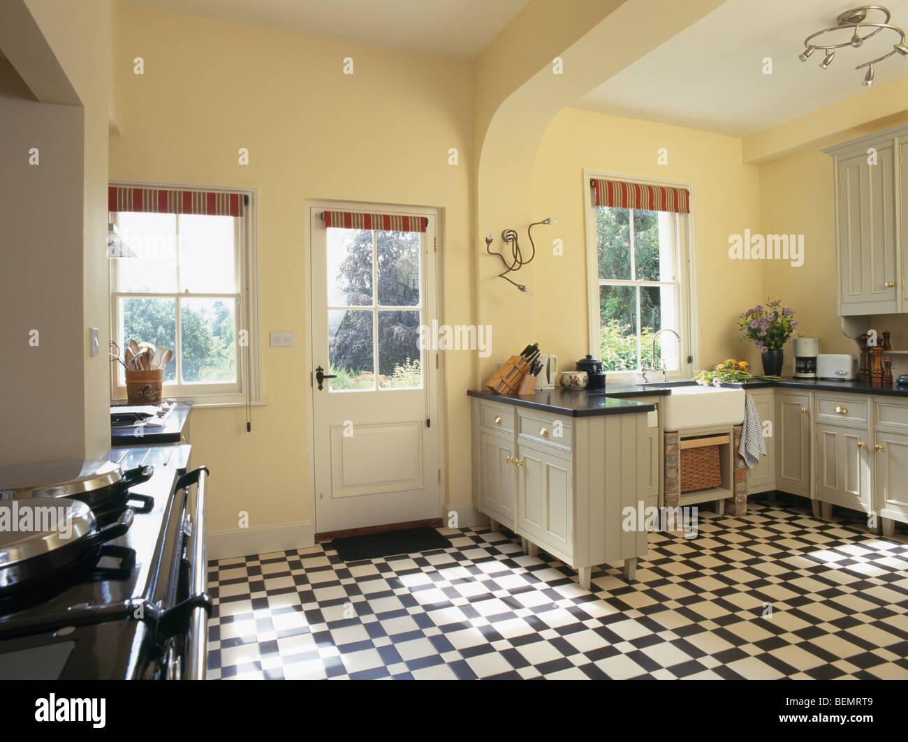 Black White Vinyl Flooring In Pastel Yellow Country Kitchen Stock