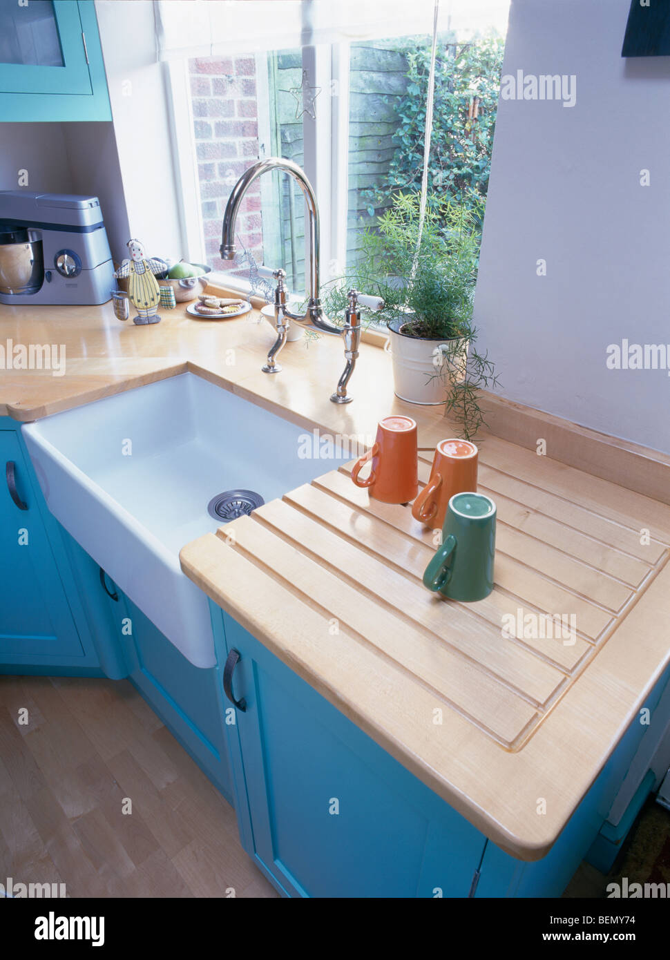 Close-up of cups on wooden draining board beside white ceramic sink ...