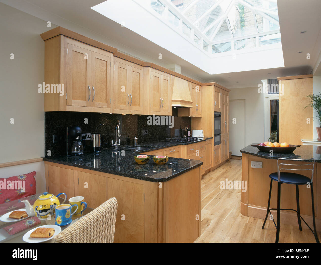 Large Skylight In Modern Kitchen Extension With Wooden Flooring And Pale  Wood Fitted Units With Granite