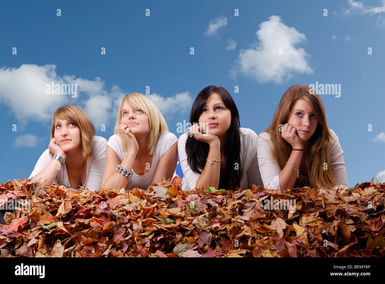 group of young woman lying in autumn leaves against a blue sky with clouds - Stock Image