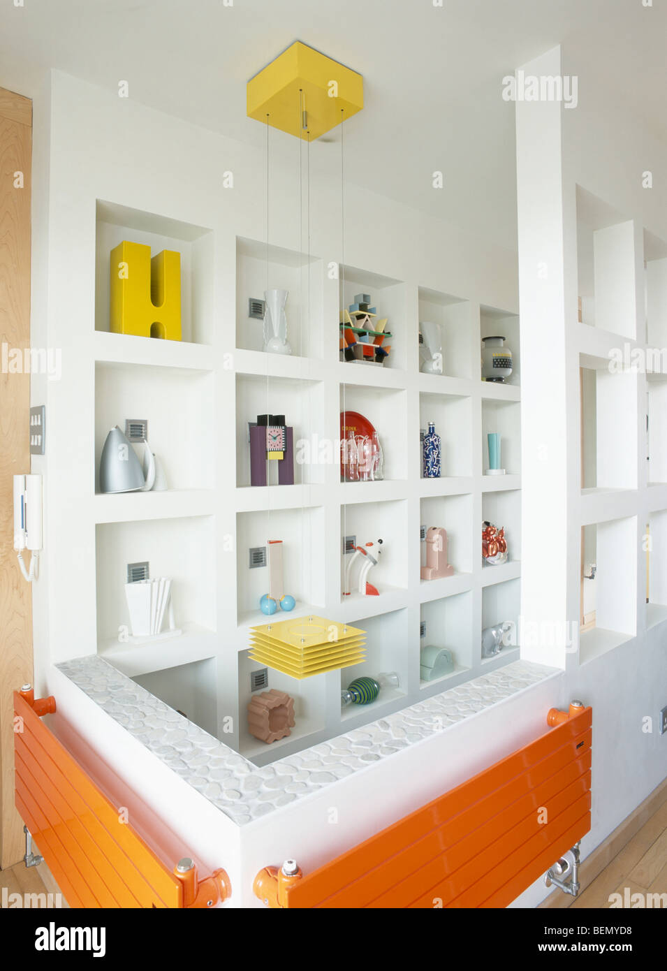 Recessed white cube shelving with collection of modern sculpture in modern white hall with orange radiators - Stock Image