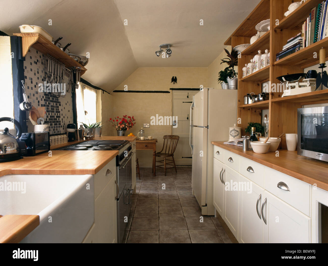 Belfast Sink In Traditional Galley Kitchen With Cream Fitted Units And Open Wooden Shelves And Flagstone Flooring Stock Photo Alamy