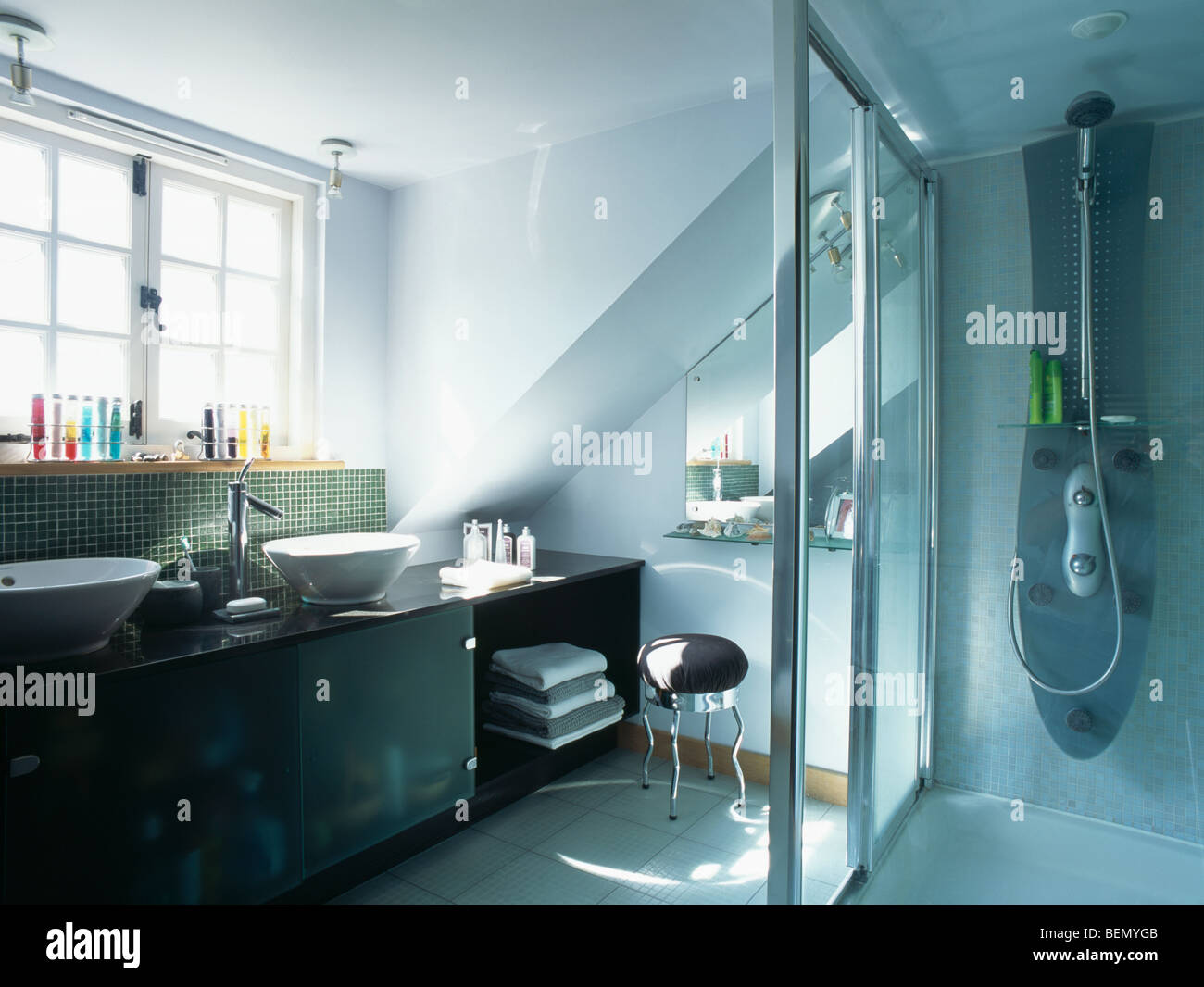 Glass wall dividing shower from vanity unit in modern white bathroom ...