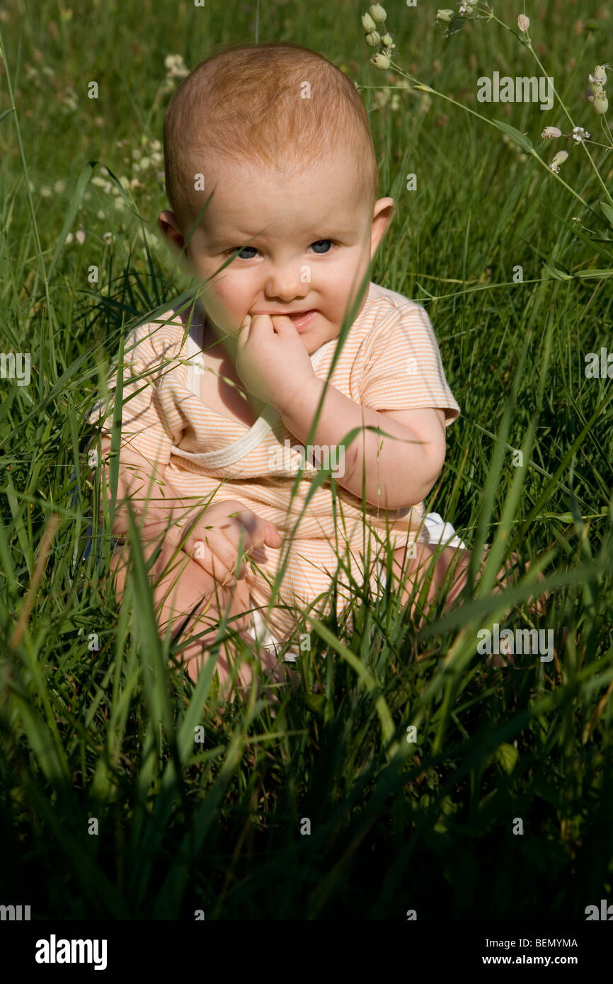 Eight months old strawberry blond baby sitting on the meadow looking at the setting sun