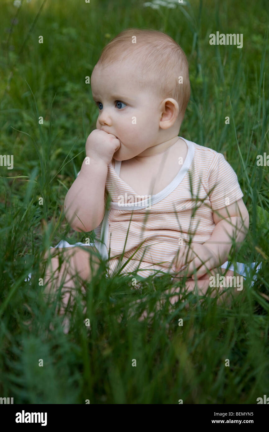 Eight months old strawberry blond baby sitting on the meadow observing thoughtfully with his hand in the mouth