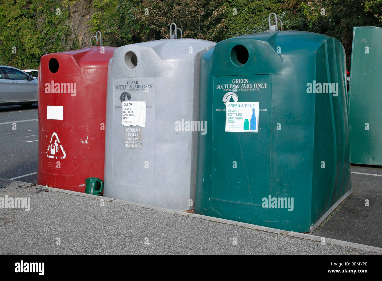 Three glass bottle and jar recycling bins in a car park. - Stock Image