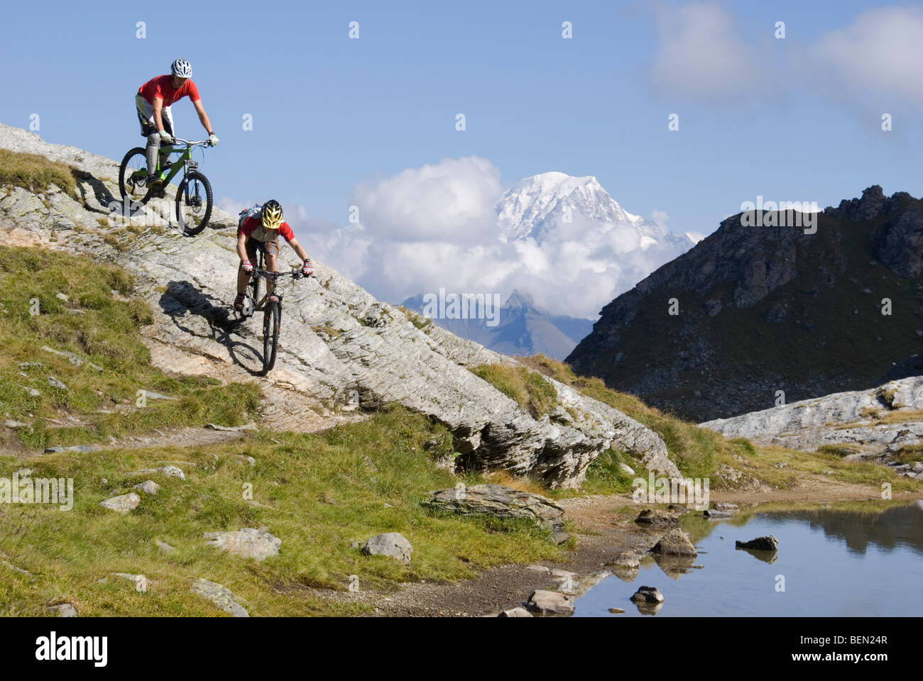 Two mountain bikers ride down a rocky slope next to a lake in the mountains near Les Arcs in the French Alps. - Stock Image