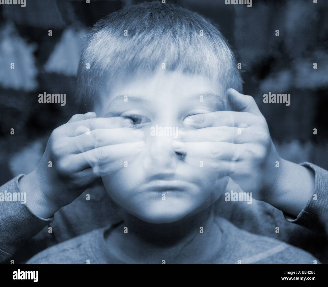 A small boy with eyes covered in an ethereal double exposure. Autism and blindness concepts - Stock Image