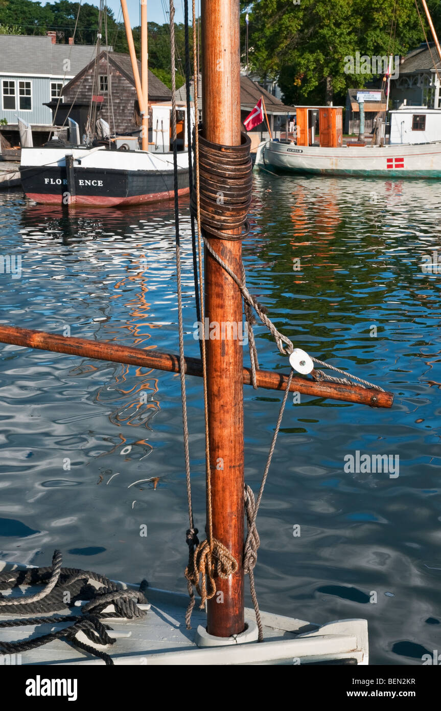 Connecticut Mystic Seaport small historic sailboat rigging detail historic fishing boats in background - Stock Image