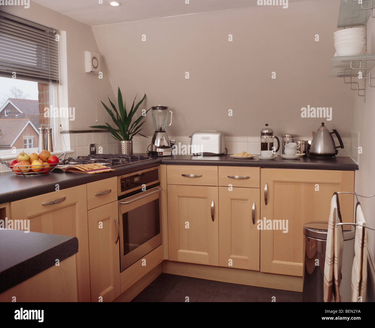 Pale wood fitted units in small apartment kitchen with small ...