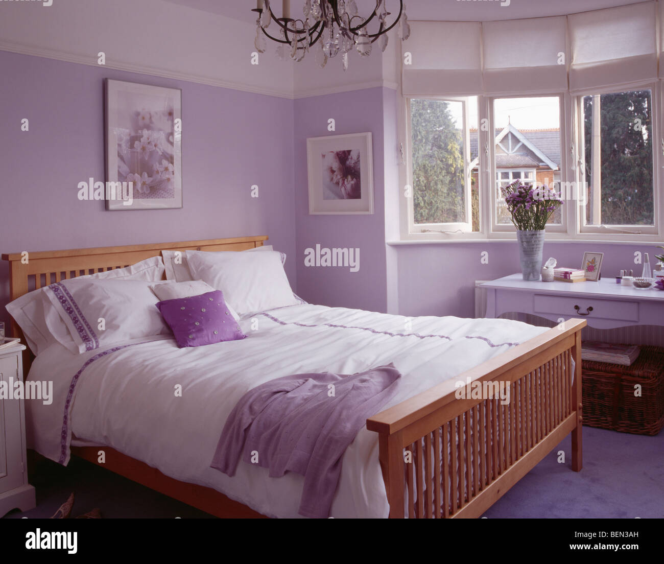 White pillows and bedlinen on wooden bed in mauve bedroom ...