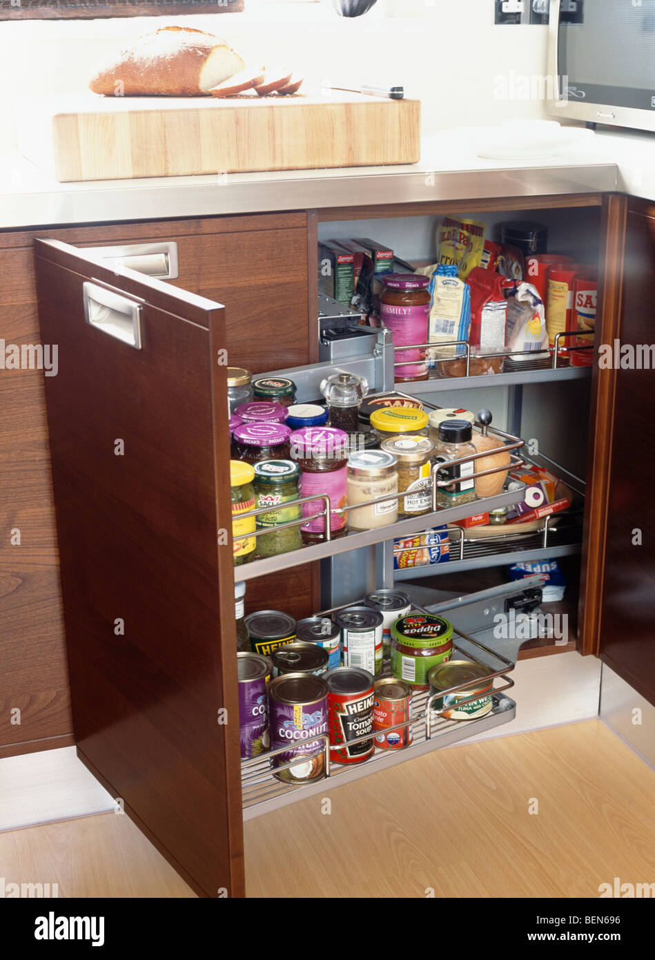 Close-up of cupboard with doors open to show jars and tins on pull-out storage shelves in modern kitchen - Stock Image