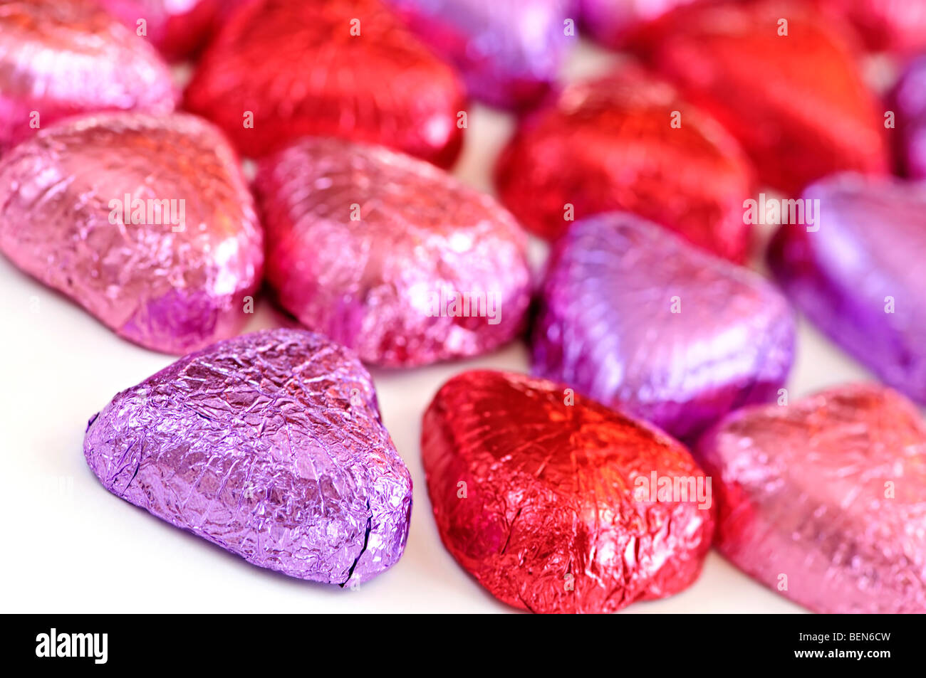 Valentine's chocolates wrapped in red and purple foil on white background - Stock Image