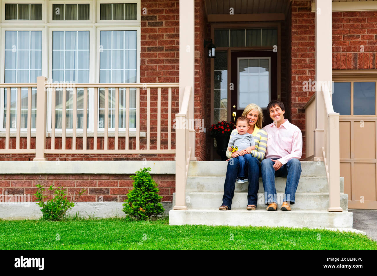 Young family sitting on front steps of house - Stock Image