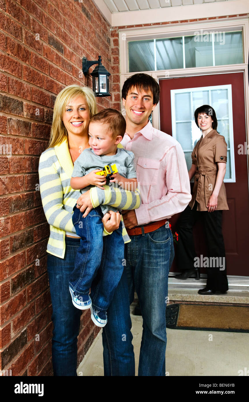 Real estate agent with family welcoming to new home - Stock Image