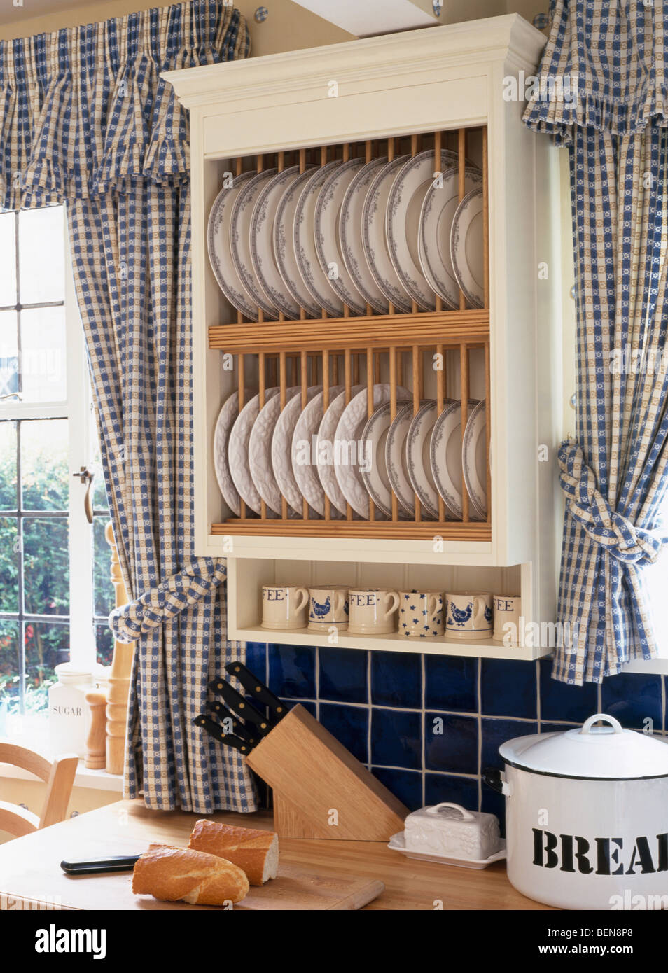 Close-up of cream plate-rack between windows with blue checked curtains in country kitchens & Close-up of cream plate-rack between windows with blue checked Stock ...