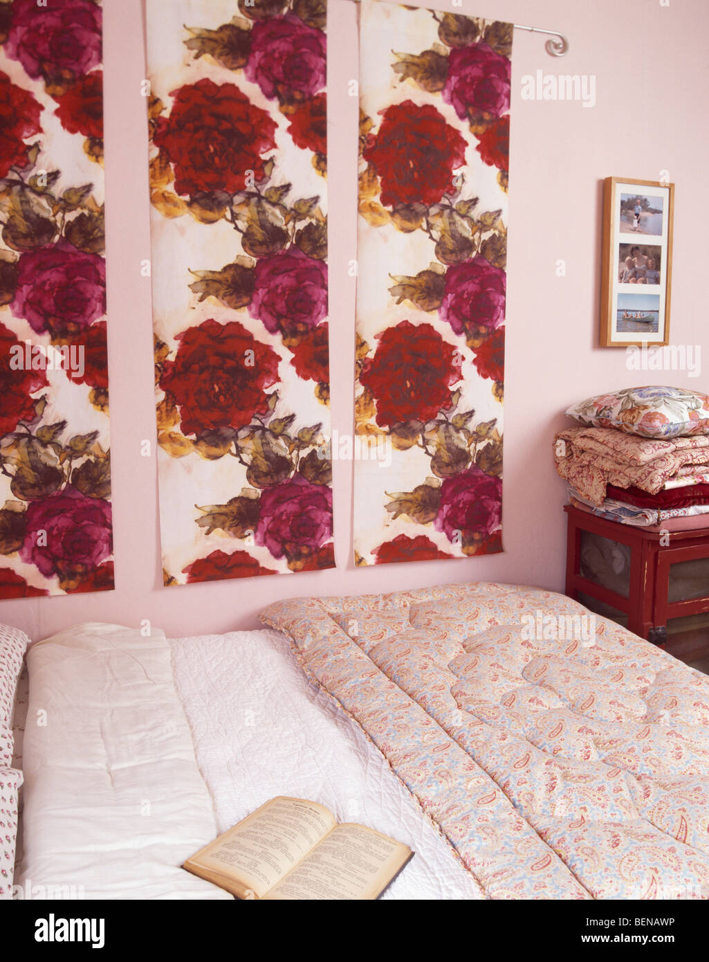 Small pink bedroom with red rose-patterned fabric panels on ...