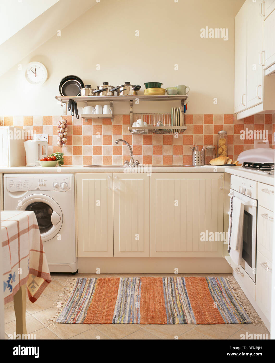 Washing Machine In Small Economy Style Attic Kitchen With Pink Rug And Wall Tiles