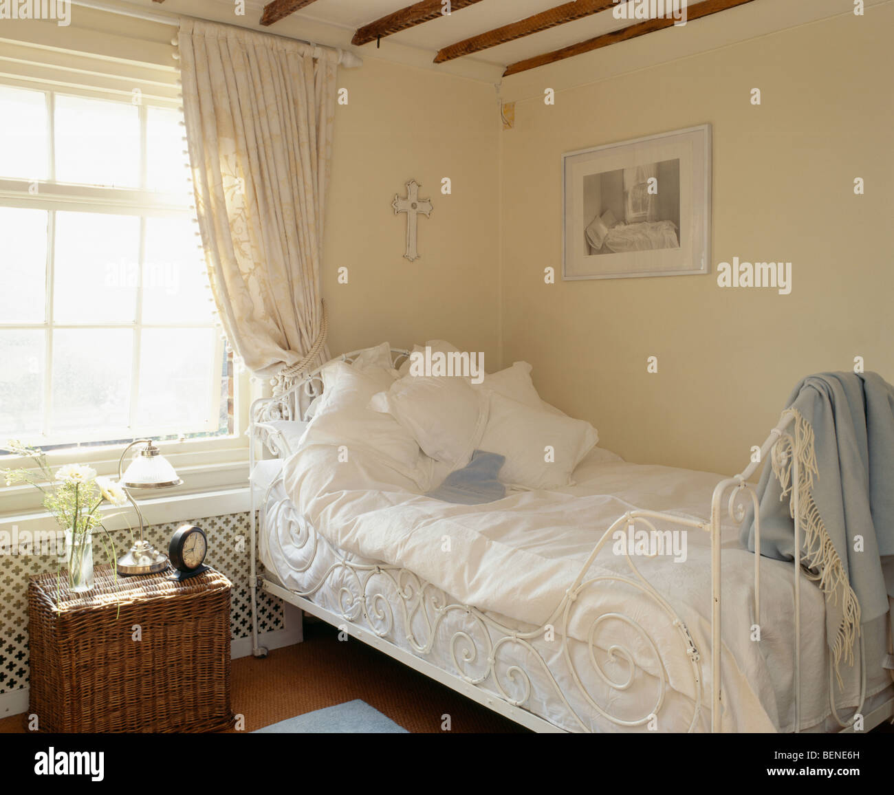 White Pillows And Bedlinen On Ornate White Cast Iron Single Bed In