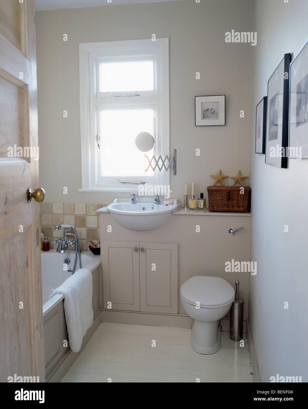 Door open to small modern cream bathroom Stock Photo - Alamy
