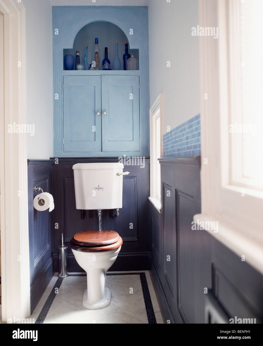 Pale Blue Fitted Cupboard Above Toilet With Mahogany Seat