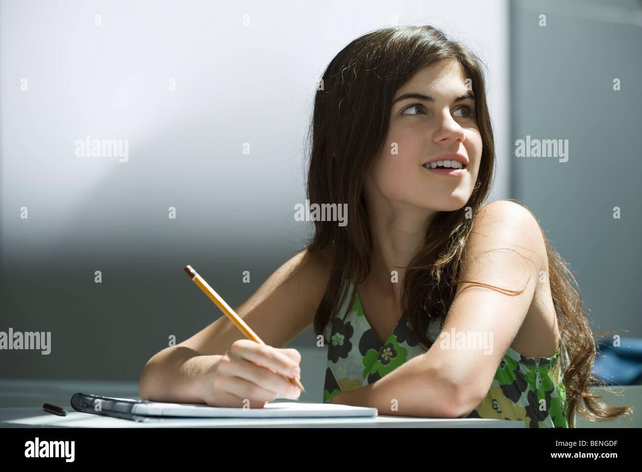 Teenage girl writing in notebook, dreamily looking away - Stock Image