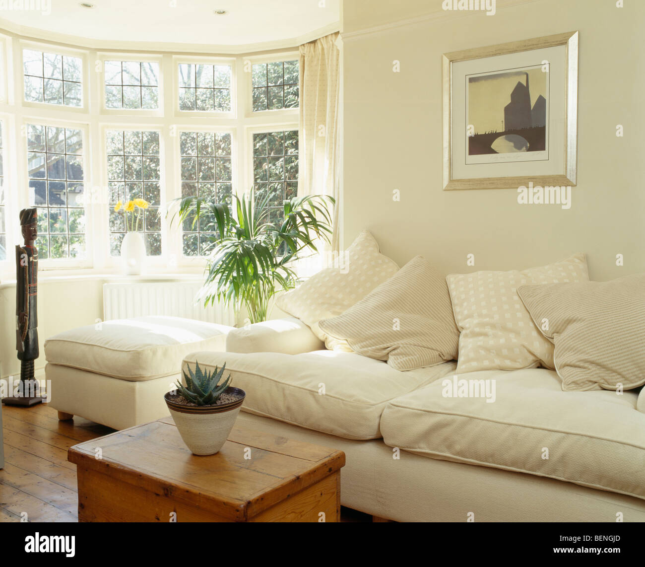 Cream sofa and pine box in sunny cream country living room with bay ...