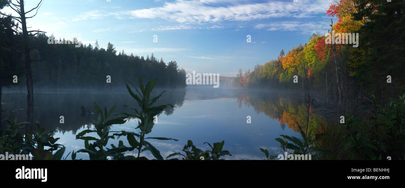Mist over Smoke lake at dawn. Beautiful panoramic fall nature scenery. Algonquin Provincial Park, Ontario, Canada. - Stock Image