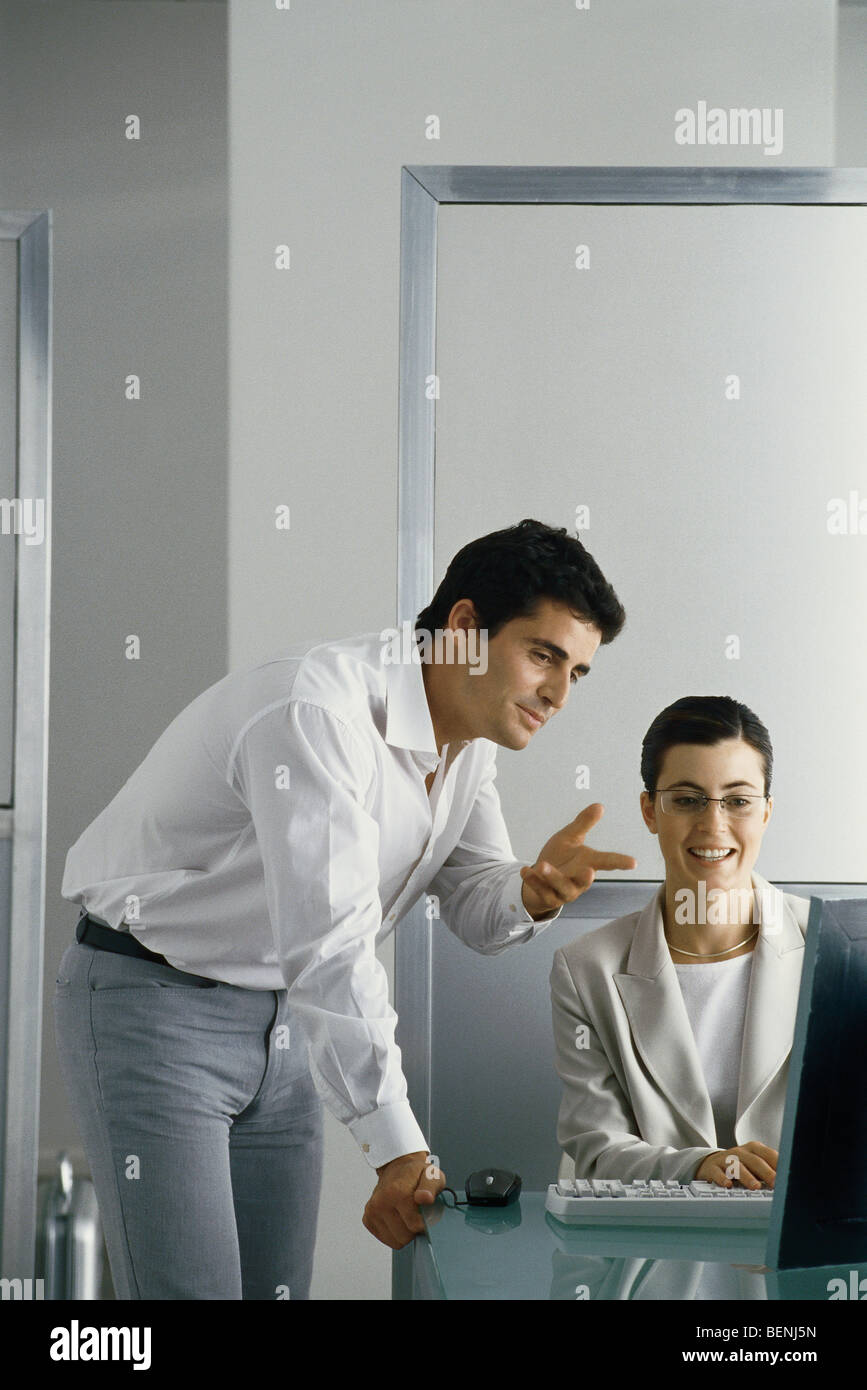 Office scene, man leaning on edge of desk speaking to female colleague, both looking at her computer screen - Stock Image