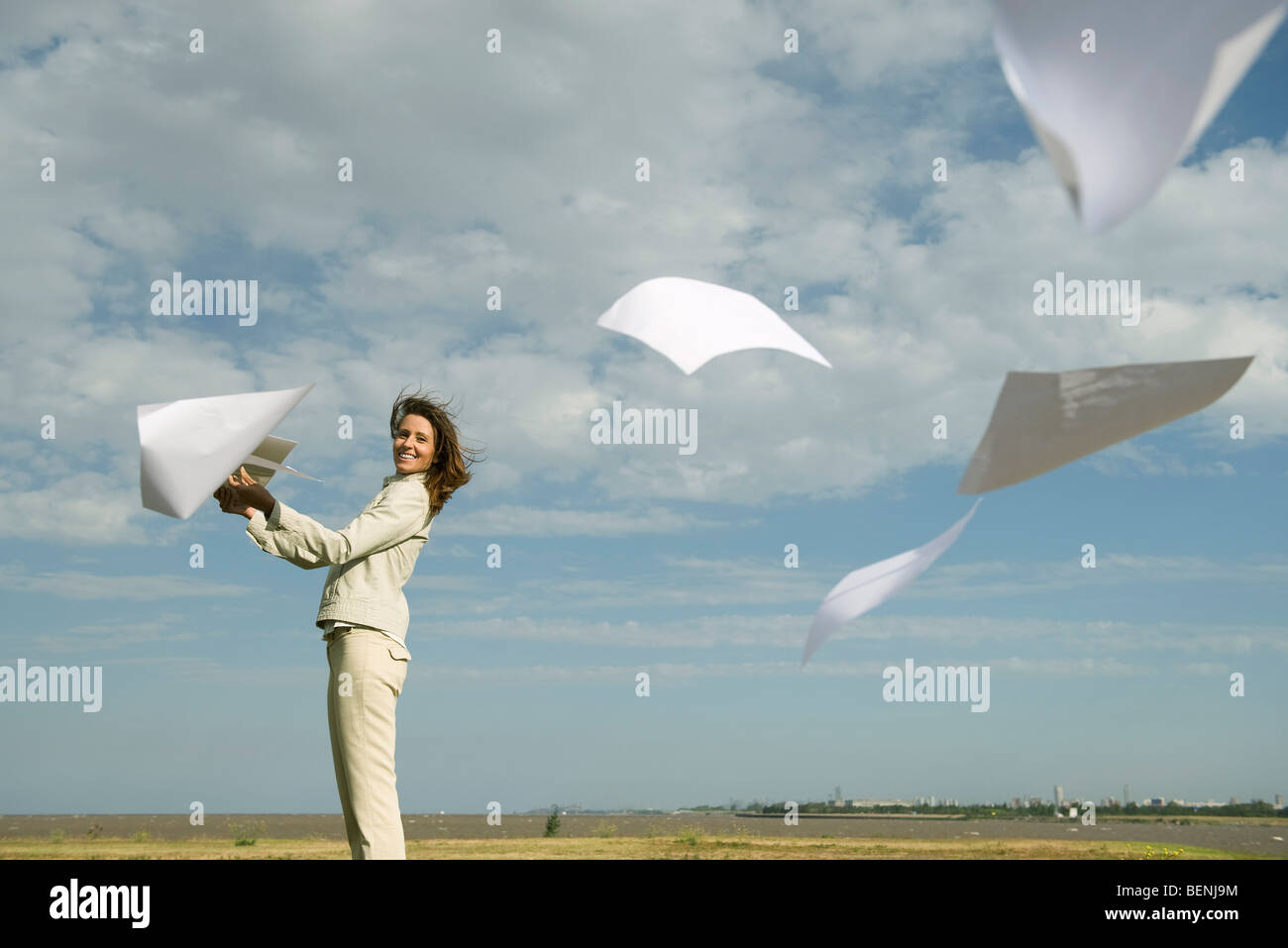 Woman outdoors tossing document into air watching pages caught by wind fly away - Stock Image