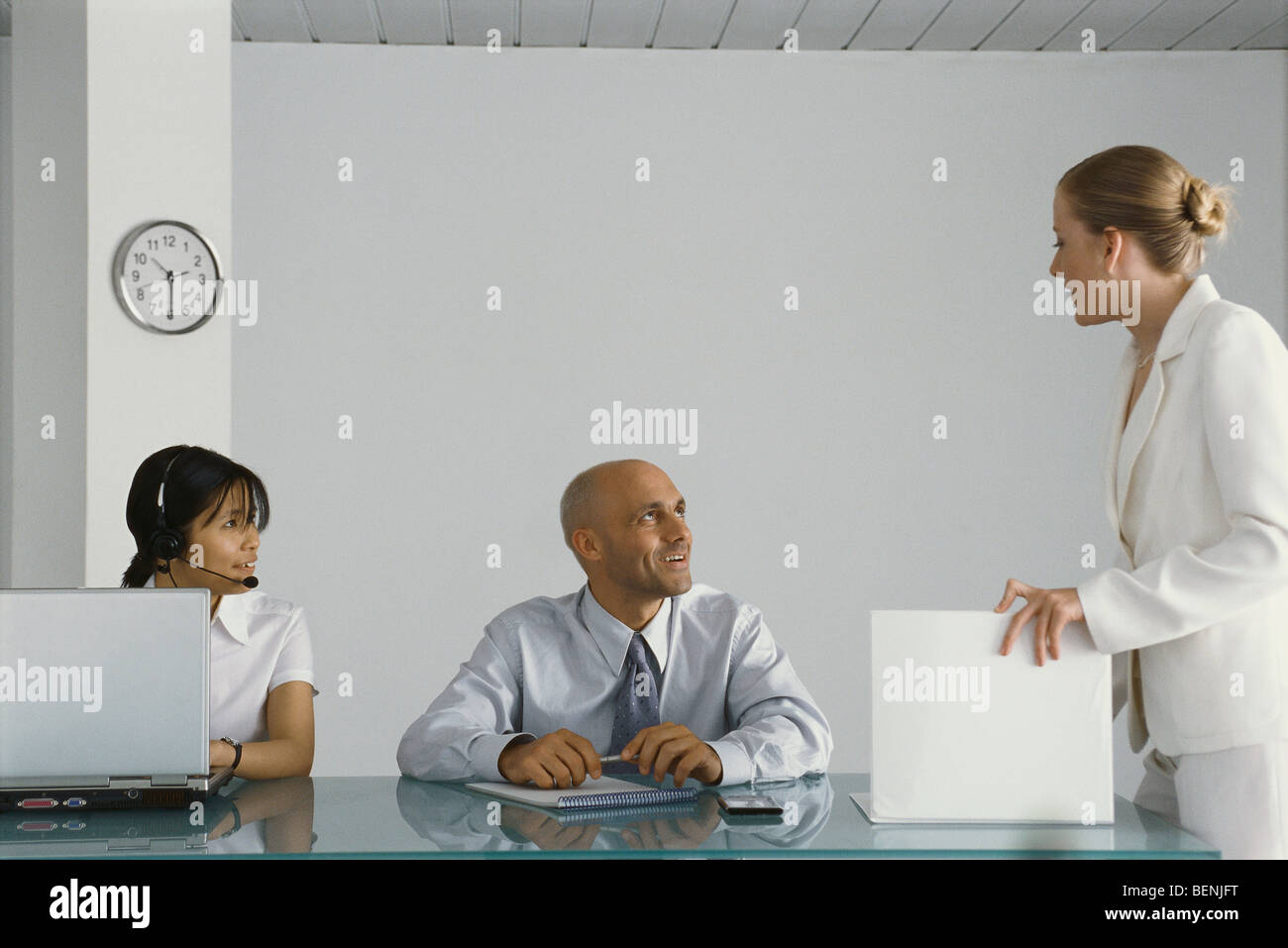 Young female executive standing by colleagues' desk, conversing - Stock Image