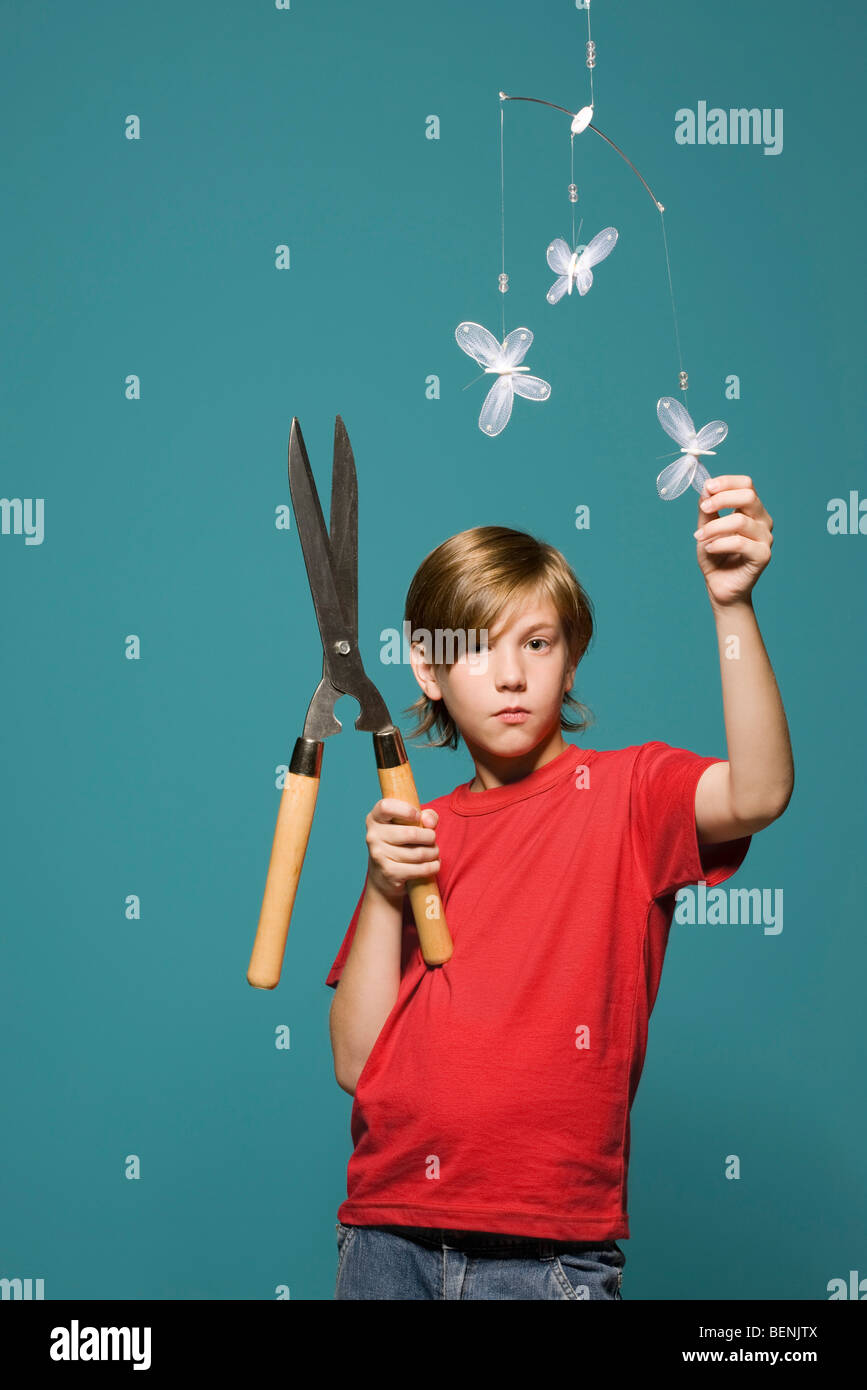 Boy standing below butterfly mobile, holding hedge clippers - Stock Image