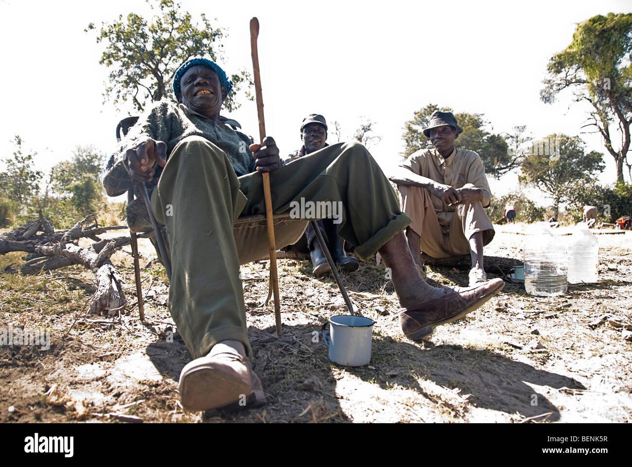 Old men sitting near the fire at their campsite, Okavango delta, Botswana, Africa. - Stock Image