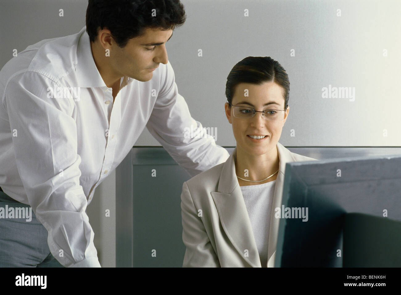 Young professional woman smiling, looking at computer screen while male colleague leans over her shoulder - Stock Image