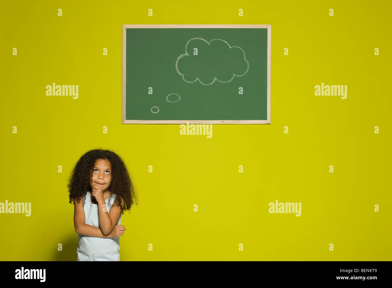 Little girl thinking, empty thought bubble on chalkboard overhead - Stock Image