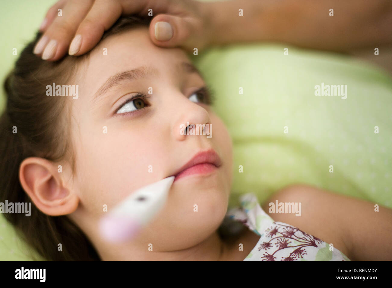 Little girl with fever, thermometer in mouth - Stock Image